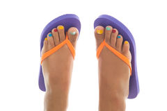 Summer feet with flip flops. Black summer feet with colorful flip flops and toe nails royalty free stock image