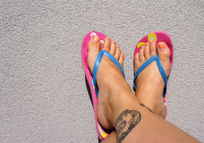 Summer feet with flip flops. Tanned legs with tattoos in flip-flops stock image