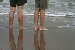 Summer feet at the Northsea. The lower legs of two boys standing in the receeding water on a sandy beach. The main color of the image is beige and grey. The legs Royalty Free Stock Photos