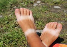 Summer feet. Suntanned feet with stripes of white skin from sandals in summer Royalty Free Stock Image