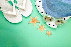 Summer female fashion outfit. Beach, vacation, travel concept. Summer female fashion outfit. Sunhat, white flip flops, polka dot towel, sunglasses and starfish stock image