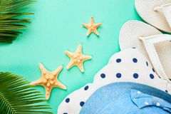 Colorful summer female fashion outfit. Beach, vacation, travel concept. Summer female fashion outfit. Sunhat, white flip flops, polka dot towel, and starfish royalty free stock photography