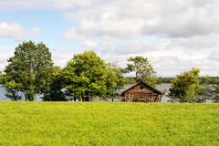 Summer field with house. Summer in the island Kizhi, Karelia. View from the island Stock Photo
