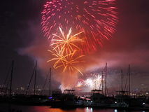 Summer fireworks over boats in harbor Stock Photography