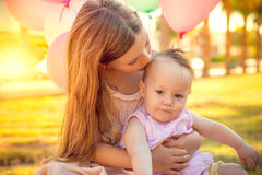 Summer first birthday. Cute little sister caring baby with balloons on party royalty free stock photo