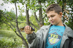 In the summer on a fishing little boy caught a large carp. Stock Images