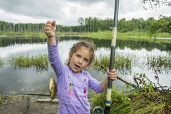In the summer on a fishing little girl caught a large carp. Stock Photography