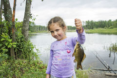 In the summer on a fishing little girl caught a large carp. Stock Image