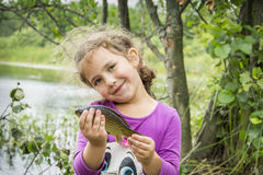 In the summer on a fishing little girl caught a large carp. Royalty Free Stock Photo