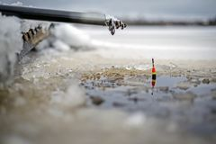 Fishing pole with float on ice Royalty Free Stock Photography