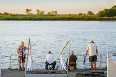 Summer fishing at sunset, unrecognizable men and woman, backs to us. Concept of active leisure, gender equality. Summer fishing at sunset, unrecognizable men and royalty free stock photography