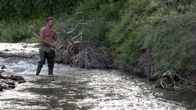 Summer Fishing for Trout. Fisherman standing in the water and turns the handle of the coil stock video footage