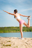 Summer fit woman stretching on beach. Summer young fit woman stretching on beach in fitness outfit Stock Images