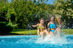 Summer fitness, kids in swimming pool have fun, smiling girls splash in water Stock Photos