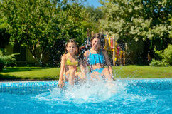Summer fitness, kids in swimming pool have fun, smiling girls splash in water Stock Photo