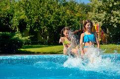 Summer fitness, kids in swimming pool have fun, smiling girls splash in water Royalty Free Stock Images