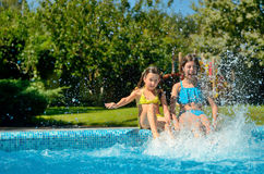 Summer fitness, kids in swimming pool have fun, smiling girls splash in water Royalty Free Stock Image