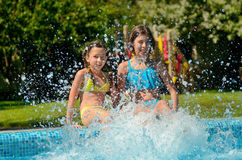 Summer fitness, kids in swimming pool have fun, smiling girls splash in water Royalty Free Stock Photos