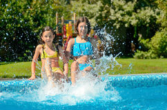 Summer fitness, kids in swimming pool have fun, smiling girls splash in water Royalty Free Stock Photography