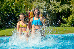 Summer fitness, kids in swimming pool have fun, smiling girls splash in water Stock Images