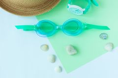 Summer flatlay with watersport goggles, hat, watch on mint and light blue background, minimalistic style, copy space stock images