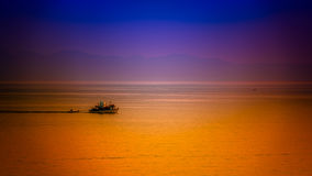 Summer flavours. Fishing boat slowly sailing at sunset Royalty Free Stock Images
