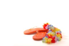 Summer Flip Flops. Orange Flip Flop sandals with a multi-colored Lei against a white backdrop with room for text Royalty Free Stock Photo