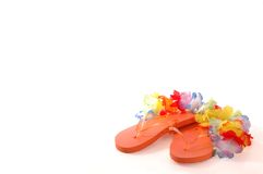 Summer Flip Flops. Orange Flip Flop sandals with a multi-colored Lei against a white backdrop with room for text Royalty Free Stock Photography