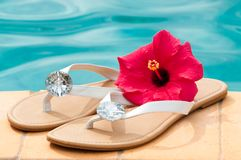 Summer Flip Flops. On the edge of luxury swimming pool with hibiscus flower royalty free stock photo