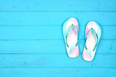Summer flip flops on a blue wood background, top view with copy space royalty free stock photography