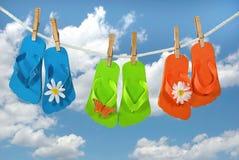Summer flip-flops on clothesline. Colorful flip-flops on a clothesline with summer sky background Stock Photo
