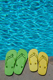 Summer Flipflops. Colored flipflops of a family of four by the swimming pool royalty free stock photo