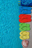 Summer Flipflops. Colored flipflops of a family of four by the swimming pool stock image