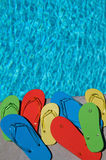Summer Flipflops. Colored flipflops of a family of four by the swimming pool stock photos