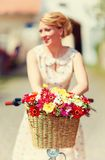 Summer flower bouquet in bicycle basket, elegant lady on background Royalty Free Stock Photos