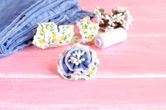 Summer flower denim brooch, jeans, thread, needles, pins, lace on pink wooden background. Art hobby for kids and women Stock Photography