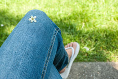 Summer Flower. A small Flower on crossed legs in Jeans Stock Image
