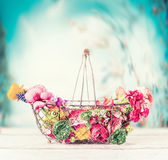Summer flowers in basket on table at turquoise blue sky background, fron view. Gardening concept stock photos