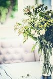 Summer flowers bunch in glass vase on table in living room with falling petals. Cozy home. And house decoration royalty free stock photography