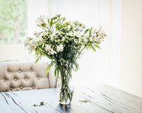 Summer flowers bunch in vase on table at window in living room with falling petals. Cozy home. And house decoration stock photo