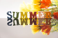 Summer and flowers. Colorful wooden letters spelling the word summer and some colorful flowers stock image