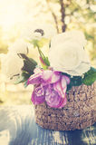 Summer flowers in dusk light. Beautiful white roses and pink peony in wooden vase on a terrace at dusk Royalty Free Stock Photography