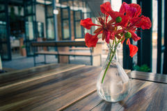 Summer flowers in a glass vase placed on a wooden table. Stock Image