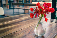 Summer flowers in a glass vase placed on a wooden table. Stock Photography