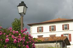 Summer flowers, lamp post and home in Sare, France in Basque Country on Spanish-French border, a hilltop 17th century village in. The Labourd province. The royalty free stock images