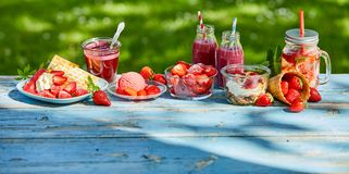 Summer food and drink strawberries. In the garden. Ice cream,waffles, smoothies, bowl and punch, desserts in the garden for coffee time royalty free stock image