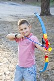 In the summer in the forest the boy shoots an arrow. In summer, in the forest, a handsome boy shoots an arrow Royalty Free Stock Images