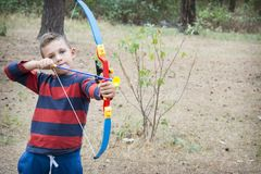 In the summer in the forest the boy shoots an arrow. stock images