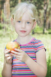 In the summer in the forest little girl eats an apple. Royalty Free Stock Photography