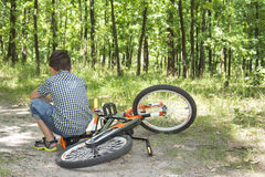 In the summer in the forest a small boy resentful sits on a bicy Stock Photo